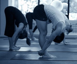 Students in forward fold practicing yoga at studio